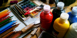 Workbench with paints, crayons and brushes