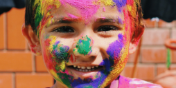 The boy's smiling face, sprinkled with colored pigment